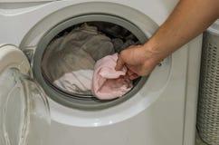De man werpt vuile wasserij in de wasmachine stock afbeeldingen