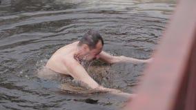 De man wordt ondergedompeld in het gat Het verharden en het zwemmen in een koude rivier stock video