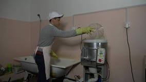 De man zet aardappels in een aardappelreinigingsmachine stock videobeelden