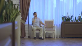 De man zit op een stoel en spreekt op de telefoon stock videobeelden