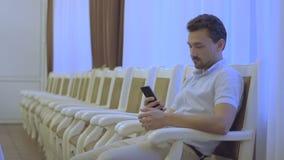 De man zit op een stoel met de telefoon stock videobeelden