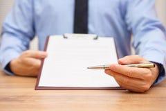 De manager biedt een pen aan om een document of een overeenkomst te ondertekenen stock foto