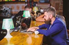 De manager creeert post geniet van koffie Het Hipster freelancer werk online het drinken koffie Mens die een koffiepauze neemt Ge royalty-vrije stock afbeelding