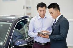 De manager die van het autohandel drijven met cliënt werken stock foto