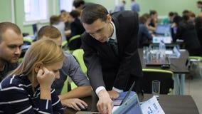 De manager en zijn medewerker om één van de teams in de spelzaken te helpen De studenten zijn verdeeld in teams en zij stock videobeelden
