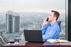 De manager harde werken in het bureau op het hoogste vloergebouw naast het venster royalty-vrije stock foto