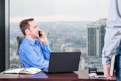De manager harde werken in het bureau op het hoogste vloergebouw naast het venster royalty-vrije stock afbeeldingen