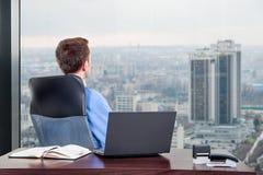 De manager harde werken in het bureau op het hoogste vloergebouw naast het venster stock afbeeldingen