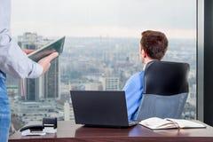 De manager harde werken in het bureau op het hoogste vloergebouw naast het venster stock foto