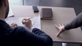 De manager op bureau wordt gegeven documenten met een tekening van materiaal op papier stock footage