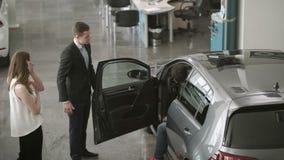 De manager toont de auto aan jong paar in het autohandel drijven aan stock video