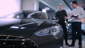 De manager toont de elektrische auto voor klant aan stock video