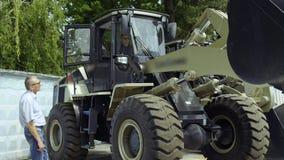 De manager toont koper aan hoe het werk de tractor stock videobeelden