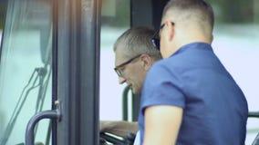 De manager toont tractor` s cabine van binnenuit aan een koper stock videobeelden