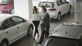De manager van autotoonzaal toont de auto's aan jong paar aan stock footage
