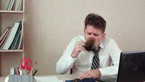 De manager van het mensenbureau heeft een hoofdpijn Hij zit bij zijn laptop met koffie stock videobeelden