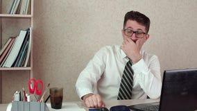 De manager van het mensenbureau met een baard en glazen, het drinken koffie voor laptop stock footage