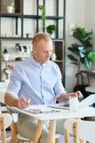 De manager van de koffiewinkel met laptop en documenten royalty-vrije stock fotografie