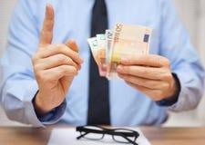 De manager waarschuwt de werknemer terwijl hij hem geld geeft royalty-vrije stock afbeeldingen