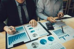 De managers gebruiken tabletten om de rapporten van verkoopkosten te analyseren en rapporten te verklaren aan werknemers berekene stock afbeeldingen
