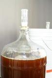 De mandefles van het glasbier met bier wordt gevuld dat stock foto's