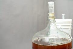 De mandefles van het glasbier met bier wordt gevuld dat stock foto