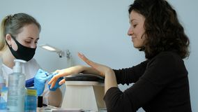 De manicure in een schoonheidssalon poetst zijn spijkers met een snijder op De cliënt evalueert het gedaane werk, volgt dicht royalty-vrije stock foto's