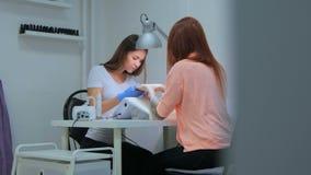 De manicure houdt handen van de cliënt in schoonheidssalon stock footage