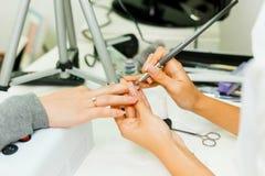 De manicure maakt het stijgen van spijkers Gebruik de nagelvijl maakt spijkervorm Handen geschoten close-up op een lichte achterg Stock Foto's
