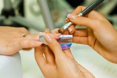 De manicure maakt het stijgen van spijkers Gebruik de nagelvijl maakt spijkervorm Handen geschoten close-up op een lichte achterg Royalty-vrije Stock Foto
