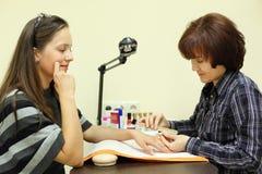 De manicure maakt manicure door nailfile voor vrouw Stock Afbeelding