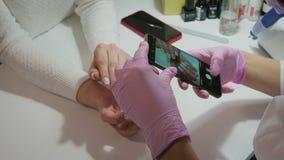 De manicure neemt beelden van de spijkers van de cliënt gebruikend de telefoon stock videobeelden