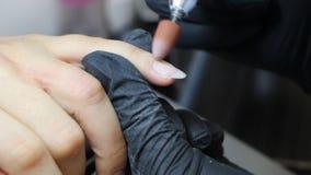 De manicure poetst opperhuid en huid rond spijkers op door boormachine stock video