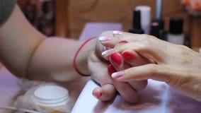 De manicure smeert de spijker met lijm en past bergkristallen met een speciaal hulpmiddel toe stock video