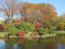 De Manicuredbomen, de struiken en andere installaties met het omringen van water leiden tot groot landschap royalty-vrije stock fotografie