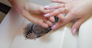 De manicuremeester maakt correcties aan roze kleur poetsmiddel gelatineren stock footage