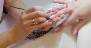De manicuremeester maakt correcties aan roze kleur poetsmiddel gelatineren stock video