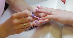 De manicuremeester past het roze poetsmiddel van het kleurengel toe stock videobeelden