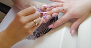 De manicuremeester past het roze poetsmiddel van het kleurengel toe stock video