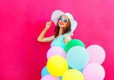 De manier die jonge vrouw met een lucht kleurrijke ballons glimlachen heeft pret op roze achtergrond stock afbeelding