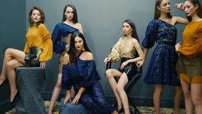 De manier stelt, vrouwelijke modellen die op achtergrond van donkere muur in studio op fotospruit stellen stock videobeelden