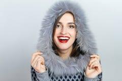 De Manier van de de winterschoonheid Mooi gezichtsmeisje met het in bonthoed gesturing emoties Professionele make-up en manicure stock foto