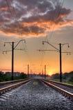 De manier van de spoorweg op zonsondergang van een zon Stock Foto