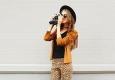 De manier ziet eruit, vrij koel jong vrouwenmodel met retro filmcamera die een elegante hoed, bruin jasje, in profiel in openluch royalty-vrije stock fotografie