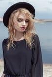 De manierfoto van jong mooi sexy meisje met nat haar in een zwarte hoed en een zwart katoen kleden zich met mooie heldere make-up Stock Fotografie