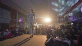 De manierindustrie, Loopbrugmodel in hoge hielen in mooi modieus kostuum van ontwerperinzameling loopt binnen op baan stock videobeelden
