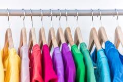 De manierkleren op kleding rekken kleurrijke kast Stock Foto's