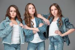 De maniermeisjes die zich en camera over grijze studioachtergrond verenigen bekijken Royalty-vrije Stock Fotografie