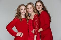 De maniermeisjes die zich en camera over grijze studioachtergrond verenigen bekijken Royalty-vrije Stock Foto's