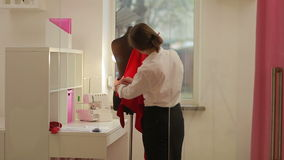 De manierontwerper kleedt maker die model in studio draperen Manierontwerper, kleermaker, naaister het aanpassen kleren stock video